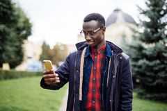 Cheerful African American man taking self portrait outdoor. Concept of social media in our life. Cheerful African American man taking self portrait. Concept of Royalty Free Stock Photography