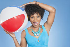 Cheerful African American woman with beach ball over colored background Royalty Free Stock Photo