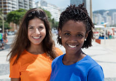 Cheerful african american woman with caucasian girlfriend. Cheerful african american women with caucasian girlfriend outdoor in the summer Royalty Free Stock Photo
