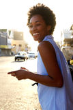 Cheerful african american woman with cell phone outdoors. Portrait of cheerful african american woman with cell phone on the city street Royalty Free Stock Image