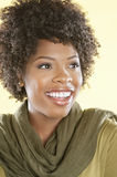 Cheerful African American woman looking away over colored background Stock Images