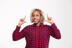 Cheerful african american woman pointing up with both hands Stock Photography