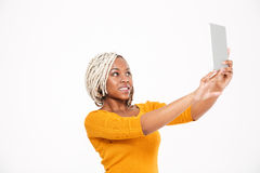 Cheerful african american woman taking selfie with tablet Stock Images