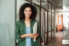 Cheerful african beautiful girl student smiling looking at camera holding books in university. Education concept. Copy space Stock Photography