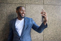 Cheerful African businessman photographing on smartphone Stock Photography