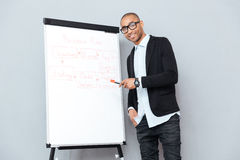 Cheerful african businessman using flipchart and pointing on business plan Stock Photos