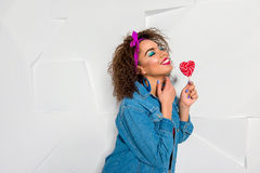 Cheerful african female keeping lollipop. Happy young woman with bright look holding candy in form of heart. Copy space Royalty Free Stock Photo