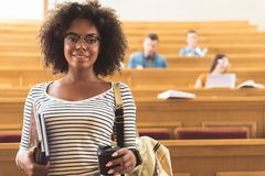 Cheerful african girl in auditory room at college. I am ready to study. Waist up portrait of pretty young mulatto women standing in front of lecture hall. She is Royalty Free Stock Image