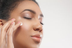 Cheerful african girl caring of her skin Royalty Free Stock Photo