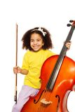 Cheerful African girl holds cello with fiddlestick. Cheerful African girl holding cello with fiddlestick ready to play standing on the white background Stock Image