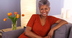 Cheerful African grandmother sitting on couch. Cheerful grandmother sitting on couch Royalty Free Stock Photo