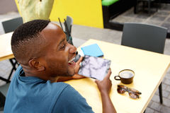 Cheerful african guy at cafe with a digital tablet Royalty Free Stock Photography