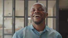 Cheerful african guy laughing sincerely indoors