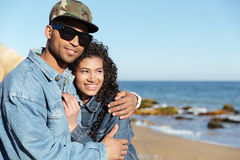 Cheerful african loving couple walking outdoors. Image of cheerful african loving couple walking outdoors at beach while hugging. Looking aside Royalty Free Stock Images