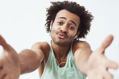 Cheerful african man in headphones rejoicing stretching hands to camera. White background. Stock Image