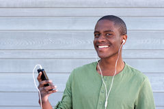 Cheerful african man listening music on mobile phone Stock Photo