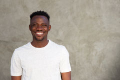 Cheerful african man smiling by wall with copy space Stock Photos