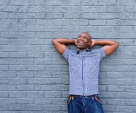 Cheerful african man standing with his hands behind head. Portrait of cheerful african man standing with his hands behind head against a gray background Royalty Free Stock Photo