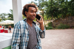 Cheerful african man talking on cell phone. Cheerful african young man talking on cell phone outdoors Royalty Free Stock Image