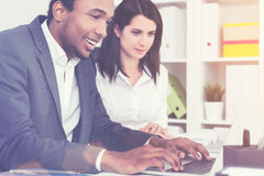 Cheerful African man working, woman watching him Stock Photography
