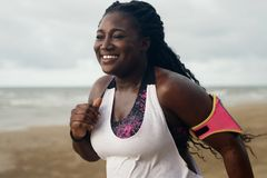 Cheerful african runner jogging during outdoor workout on beach royalty free stock photo