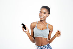 Cheerful african sportswoman listening music from blank screen cell phone Stock Image