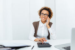 Cheerful african woman accountant using calculator talking on mobile phone Stock Photography