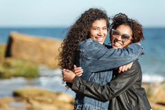 Cheerful african woman friends walking outdoors at beach. Photo of cheerful african women friends walking outdoors at beach. Looking at camera while hugging Stock Image