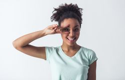 Beautiful Afro-American girl. Cheerful Afro-American girl in casual clothes is gesturing, looking at camera and smiling, isolated on white Royalty Free Stock Images