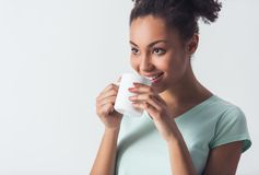 Beautiful Afro-American girl. Cheerful Afro-American girl in casual clothes is holding a cup, looking away and smiling, isolated on white stock images