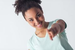 Beautiful Afro-American girl. Cheerful Afro-American girl in casual clothes is pointing and looking at camera and smiling, isolated on white Royalty Free Stock Image