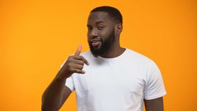 Cheerful Afro-American man showing call me gesture, getting acquainted on party. Stock footage stock footage