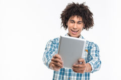 Cheerful afro american man using tablet computer. Portrait of a cheerful afro american man using tablet computer isolated on a white background Royalty Free Stock Image