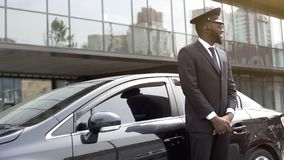 Cheerful Afro-American taxi service driver expecting passengers near luxury car. Stock photo Stock Photo