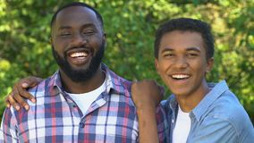 Cheerful afro-american teenager hugging smiling father, happy family portrait