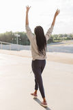 Cheerful afro-american teenager is raiding the hands up while dancing on the street. Back view. Cheerful afro-american teenager is raiding the hands up while Royalty Free Stock Image