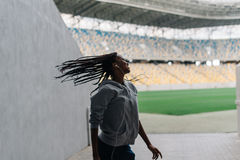 The cheerful afro-american teenager is shaking head at the background of the stadium. Royalty Free Stock Image