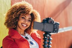 Smiling female blogger shooting for her video blog royalty free stock image