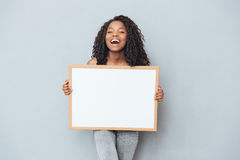 Cheerful afro american woman showing blank board Stock Image