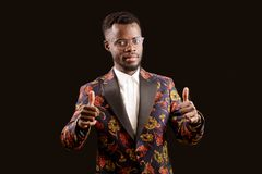 Cheerful Afro singer showing gesture of cool class. Cheerful Afro singer showman in fashionable suit showing gesture of cool class . good job. praise Stock Images