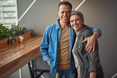 Cheerful aged couple embracing tenderly in cafe. Enjoyable meeting. Waist up portrait of happy excited aged women and men tenderly embracing together while being royalty free stock photos
