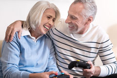 Cheerful aged couple relaxing at home. We laughing together. Cheerful smiling aged couple holding game consoles while sitting on the sofa and laughing together royalty free stock photography