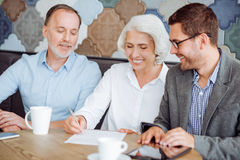 Cheerful aged couple signing the contranct stock photos