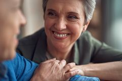 Cheerful aged lady looking with love to man. Enjoyable meeting. Close up portrait of cheerful aged women looking with love to her male friend holding hands stock images