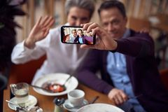 Cheerful aged lady and man making selfie in cafe. Enjoyable meetings. Close up portrait of mobile phone screen with happy smiling aged male and female making royalty free stock photo