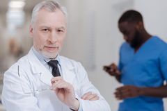 Cheerful aged physician expressing positivity at work Stock Image