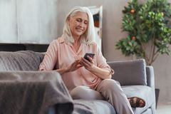 Cheerful aged woamn going to make a call Royalty Free Stock Image