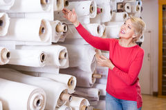Cheerful aged woman customer looking for beautiful fabric in tex Stock Photography