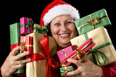 Cheerful Aged Woman Embracing Wrapped Presents. Honorable lady brimming over with joy is  pressing ten wrapped Christmas presents to her chest. Santa Claus hat Stock Photo