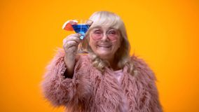 Cheerful aged woman in funny pink outfit raising toast, drinking blue cocktail stock photo